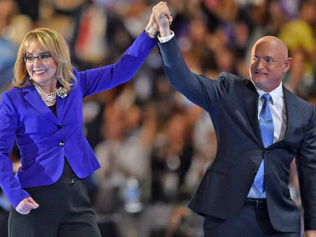 Former Congresswoman Gabby Giffords (L) and her husband and former astronaut Mark Kelly leave the stage during the third evening session of the Democratic National Convention at the Wells Fargo Center in Philadelphia, Pennsylvania, July 27, 2016. / AFP / Nicholas Kamm (Photo credit should read NICHOLAS KAMM/AFP/Getty Images)