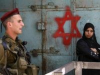 An Israeli soldier keeps guard near a Palestinian woman standing by a Star of David graffiti sprayed by Israeli settlers near an army checkpoint in the centre of the occupied West Bank city of Hebron on May 18, 2009 during a visit by a delegation of ultra-nationalist Israeli MPs protesting against Israeli Prime Minister Benjamin Netanyahu's promotion of the easing of restrictions on Palestinians.