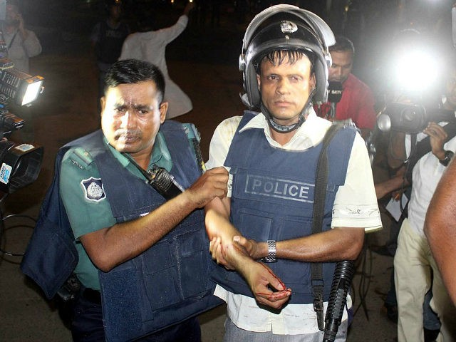 BANGLADESH, Dhaka : An injured policeman is escorted away by his colleague after an attack in Dhaka, Bangladesh, July 2, 2016. Gunmen have shot dead two police officials, police said, in the first attack on a foreign restaurant in Bangladesh claimed by Islamic State (IS) group jihadists. The gunmen stormed the restaurant in Bangladesh capital Dhaka's diplomatic enclave Gulshan on Friday night at about 9:00 p.m. local time. At least 40 people including two more senior police officials were injured in the incident.