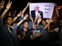 "FILE -- In this July 14, 2015 file photo, young Iranian men cheer and show victory signs while holding a picture of Foreign Minister Mohammad Javad Zarif, reading ""Zarif is Mosaddegh of our time,"" comparing Zarif to Mohammad Mosaddegh, Iran's legendary prime minister during the 1950s who nationalized the country's …"