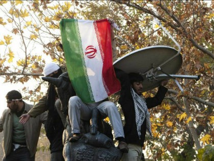 Iranian protesters remove a satellite dish from a building near the gate of the British Embassy in Tehran, Nov. 29, 2011. (photo by REUTERS/Raheb Homavandi)