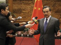 China's Foreign Minister Wang Yi (R) speaks to journalists in front of a Chinese national flag after a meeting with Japan's ambassador to China Masato Kitera (not seen), at the Ministry of Foreign Affairs in Beijing, December 26, 2013. China's Foreign Minister summoned Japan's ambassador to China on Thursday to …