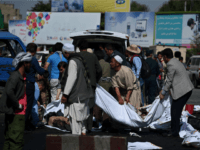 Afghan volunteers carry the bodies of victims at the scene of a suicide attack that targeted crowds of minority Shiite Hazaras during a demonstration at the Deh Mazang Circle of Kabul on July 23,2016.