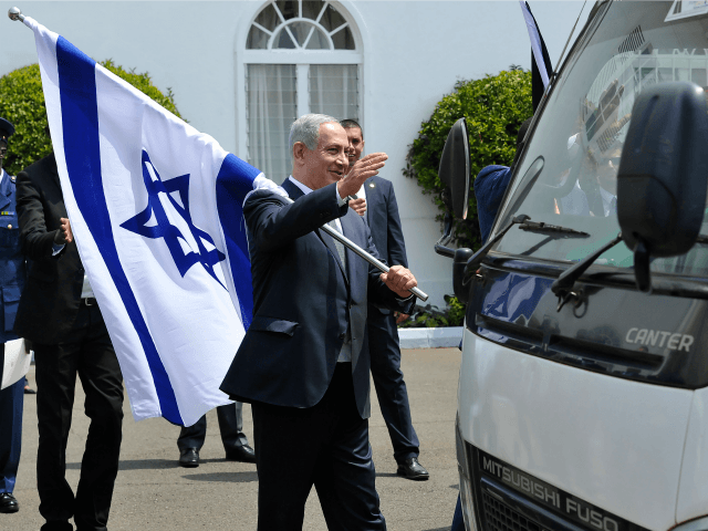 Israeli Prime Minister, Benjamin Netanyahu (L) holds an Israeli national flag after a join press conference with and Kenya's President in July 5, 2016 at the State House, in Nairobi. Netanyahu visits Kenya on the second leg of a four nation tour of sub-Saharan Africa. / AFP / SIMON MAINA …