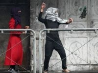 A Palestinian young woman throws stones towards Israeli security forces during clashes in the West Bank town of Hebron on October 7, 2015. New violence rocked Israel and the Israeli occupied West Bank, including an incident in which men thought to be undercover Israeli police opened fire on Palestinian stone throwers they had infiltrated, wounding three of them. AFP PHOTO / HAZEM BADER (Photo credit should read HAZEM BADER/AFP/Getty Images)