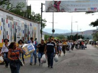 Venezuelans carrying groceries cross the Simon Bolivar bridge from Cucuta in Colombia back to San Antonio de Tachira in Venezuela, on July 10, 2016. Thousands of Venezuelans crossed Sunday the border with Colombia to take advantage of its 12-hour opening after it was closed by the Venezuelan government 11 months …