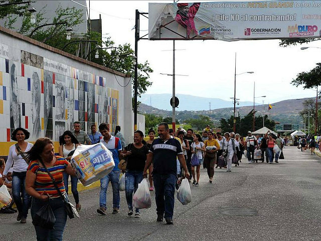 Venezuelans carrying groceries cross the Simon Bolivar bridge from Cucuta in Colombia back to San Antonio de Tachira in Venezuela, on July 10, 2016. Thousands of Venezuelans crossed Sunday the border with Colombia to take advantage of its 12-hour opening after it was closed by the Venezuelan government 11 months ago. Venezuelans rushed to Cucuta to buy food and medicines which are scarce in their country. / AFP / GEORGE CASTELLANOS (Photo credit should read GEORGE CASTELLANOS/AFP/Getty Images)