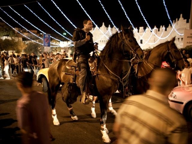 Horse mounted policemen stand guard under lights decorating the Damascus Gateon during the Muslim holy fasting month of Ramadan on August 8, 2011, at the old city of Jerusalem, Israel. (Photo by Uriel Sinai/Getty Images)