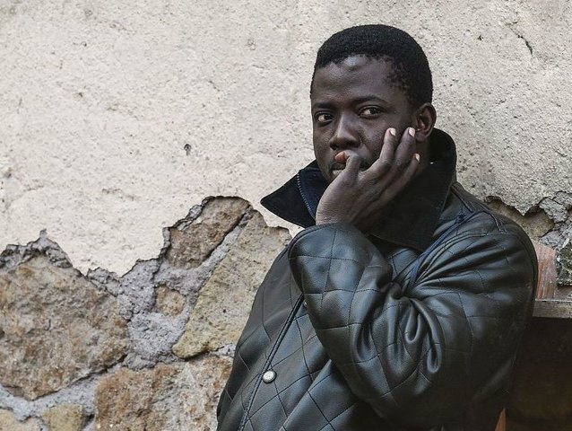 "A migrant waits during the evacuation of the ""Baobab"" migrant reception centre next to the Tiburtina train station in Rome on December 4, 2015. The authorities of the Department for Social Policy of Rome announced on December 1, 2015 the evacuation of the reception centre. / AFP / ANDREAS SOLARO …"