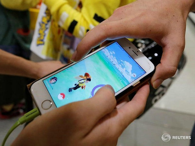Men play the augmented reality mobile game ''Pokemon Go'' by Nintendo on a mobile phone in Tokyo, Japan July 22, 2016. REUTERS/TORU HANAI - RTSJ4LO