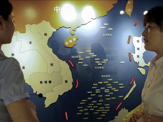 In this Tuesday, July 12, 2016 photo, workers chat near a map of South China Sea on display at a maritime defense educational facility in Nanjing in east China's Jiangsu province. China blamed the Philippines for stirring up trouble and issued a policy paper Wednesday calling the islands in the …