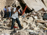 A Syrian man reacts as rescuers look for victims under the rubble of a collapsed building following a reported air strike on the rebel-held neighbourhood of Sakhur in the northern city of Aleppo on July 19, 2016. Civilians in rebel-held parts of Syria's Aleppo expressed fears on July 18, 2016 …