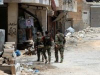 Syrian army soldiers patrol in government-controlled Aleppo's al-Khalidiya area where the army progressed towards the industrial zone of al-Layramoun and Bani Zeid on June 28, 2016. Aleppo was once the country's commercial hub but now lies divided between government forces in the west and rebels in the east. / AFP / GEORGES OURFALIAN (Photo credit should read GEORGES OURFALIAN/AFP/Getty Images)