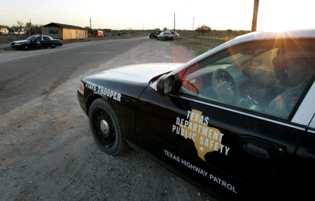 A Texas State Trooper is shown sitting in his vehicle right, as he and others maintain a roadblock miles from a religious retreat built by polygamist leader Warren Jeffs, Sunday, April 6, 2008, in Eldorado, Texas. (AP Photo/Tony Gutierrez)
