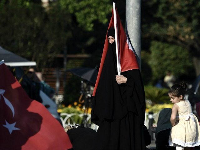 A veiled woman holds a Turkish flag during a demonstration in Istanbul in support the government on July 16, 2016, following a failed coup attempt. Turkish authorities said they had regained control of the country on July 16 after thwarting a coup attempt by discontented soldiers to seize power from …