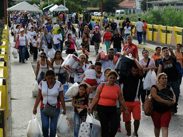 Venezuela, San Antonio del Táchira : Venezuelans carrying groceries cross the Simon Bolivar bridge from Cucuta in Colombia back to San Antonio de Tachira in Venezuela, on July 10, 2016. Thousands of Venezuelans crossed Sunday the border with Colombia to take advantage of its 12-hour opening after it was closed by the Venezuelan government 11 months ago. Venezuelans rushed to Cucuta to buy food and medicines which are scarce in their country. / AFP PHOTO / GEORGE CASTELLANOS