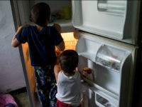 Young childern look in an empty refrigerator at a home in the Catia neighborhood on the outskirts of Caracas, Venezuela, on Thursday, June 30, 2016. In an attempt to regain control, President Nicolas Maduro has tapped loyal neighborhood groups, called Local Committees for Supply and Production (CLAPs), and put them in charge of distributing as much as 70 percent of the nation's food. Photographer: Manaure Quintero/Bloomberg via Getty Images