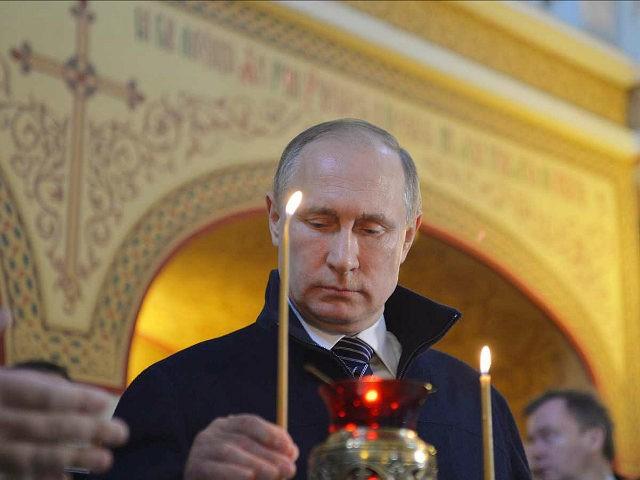 Russian President Vladimir Putin puts a candle in a hospital church while visiting the Dima Rogachev Children's Haematology Center in Moscow, Russia, Wednesday, June 1, 2016. (Alexei Druzhinin/Sputnik, Kremlin Pool Photo via AP)