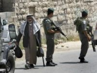 An elderly Palestinian man walks past Israeli border guards in the centre of the occupied West Bank city of Hebron on May 18, 2009 during a visit by a delegation of ultra-nationalist Israeli MPs protesting against Israeli Prime Minister Benjamin Netanyahu's promotion of the easing of restrictions on Palestinians.