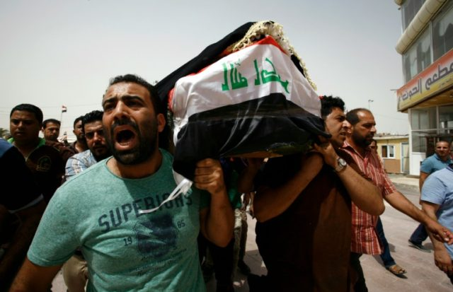 Iraqi men carry a coffin in Najaf during a funeral procession for the victims of a suicide bombing that ripped through Baghdad's busy shopping district of Karrada, on July 3, 2016