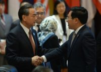 China's Foreign Minister Wang Yi (L) shakes hands with Vietnam's Foreign Minister Pham Binh Minh during the ASEAN-China meeting on the sidelines of the ASEAN annual ministerial meeting and the Regional Security Forum, in Vientiane, on July 25, 2016