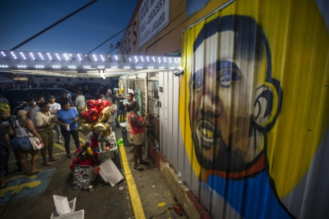 Protesters gather in front of a mural of Alton Sterling on the wall of a convenience store in Baton Rouge, Louisianna where Sterling was shot dead by police