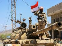 A Yemeni fighter loyal to the country's exiled president salutes at a checkpoint in the southwestern city of Taez