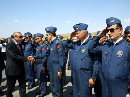 Turkish President Recep Tayyip Erdogan (L) shakes hands with security forces during his visit to the Police Special Operation Department's headquarters in Ankara on July 29, 2016