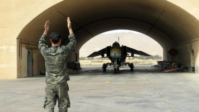 A Syrian army jet is guided out of the hangar at Dmeir military airport, 50 km north-east of Damascus, on April 8, 2016