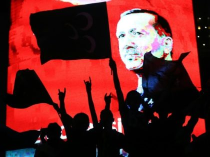 Supporters stands in front of a screen displaying a portrait of Turkish President Recep Tayyip Erdogan during a rally in Ankara on July 20, 2016