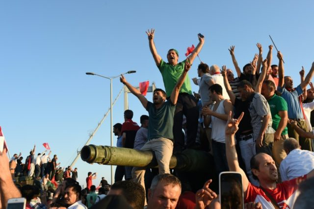 People react after taking over military position on the Bosphorus bridge in Istanbul, on July 16, 2016