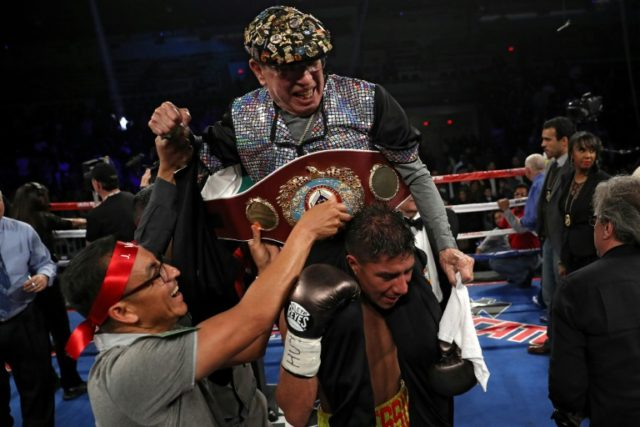 Jessie Vargas celebrates by carrying his godfather and cutman Rafael Garcia after defeating Sadam Ali for the vacant WBO welterweight title