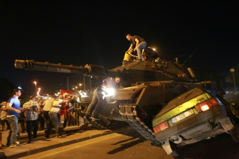 Pro-government supporters climb onto a tank as it runs over a car during a protest in Ankara agaist a military coup