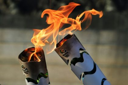 Brazilian residents pass the Olympic torch at Independence Park in Sao Paulo, Brazil on July 24, 2016