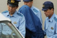 Murder suspect Satoshi Uematsu (C, in blue shroud) is escorted to a van heading to the prosecutor's office, from a local police station in Sagamihara, Japan's Kanagawa prefecture, on July 27, 2016