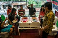 Customers enjoy a meal at the 'Jamban Cafe' in the city of Semarang on Indonesia's Java island, a small eatery where a handful of diners sit on upright toilets around a table where food is served in two squat toilets