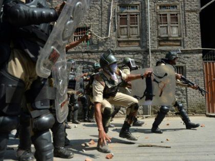 Indian police personnel prepare to throw stones towards Kashmiri protestors during clashes in Srinagar on July 1, 2016