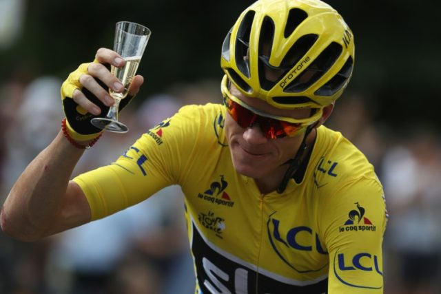 Great Britain's Chris Froome is enjoys a glass of champagne as he rides during final stage of the Tour de France on July 24, 2016