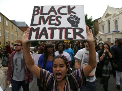 "A women holds up a placard with the slogan ""Black Lives Matter"" as people march in Brixton, south London to protest against police brutality in the US after two recent incidents where black men have been shot and killed by police officers"