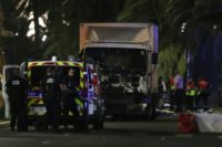Police officers and rescue workers stand near a van that ploughed into a crowd leaving a fireworks display in the French Riviera town of Nice on July 14, 2016