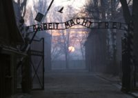 "Main gate entering the Nazi Auschwitz death camp at sunrise with the infamous sign reading ""Arbeit macht frei"" (Work sets you free)"