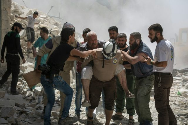 Syrians carry a wounded man following a reported barrel bomb attack by government forces in the opposition-held district of Al-Mashhad near Aleppo on July 26, 2016