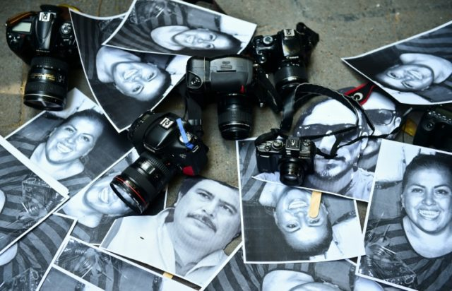 Photos of killed journalists and cameras lie outside the Veracruz state representation office during a journalists protest in Mexico City on February 11, 2016