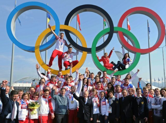 Russia's President Vladimir Putin (C) poses for a photo with Russian athletes, winners of the 2014 Winter Olympics, in Sochi