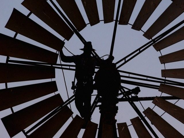 A file photo shows Pineview Station owner Mark Lacey repairing one of his broken windmills on October 25, 2002 in Broken Hill, New South Wales, Australia.