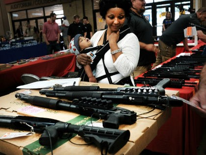 FORT WORTH, TX - JULY 10: A woman admires weapons at a gun show where thousands of different weapons are displayed for sale on July 10, 2016 in Fort Worth, Texas. The Dallas and Forth Worth areas are still mourning the deaths of five police officers last Thursday evening by …