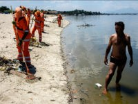 City cleaners collect floated debris on a beach at Guanabara bay in Rio de Janeiro, Brazil on December 26, 2015. The bay, where the nautical sports of Rio 2016 Olympic Games will take place, receives sewage directly from the city system. AFP PHOTO / YASUYOSHI CHIBA / AFP / YASUYOSHI …