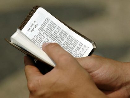 A worshiper holds a small Bible at an outdoor Sunday service 04 September 2005 at the East Howard Baptist church which was badly damaged by Hurricane Katrina in Biloxi, Mississippi.