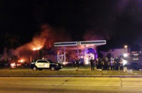 Authorities respond near a burning gas station as dozens of people protest following the fatal shooting of a man in Milwaukee, Saturday, Aug. 13, 2016. A crowd of protesters skirmished with police Saturday night in the Milwaukee neighborhood where an officer shot and killed a man after a traffic stop …