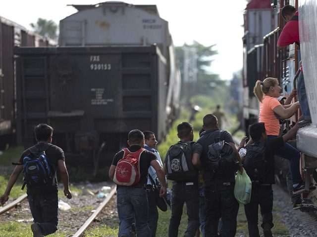 In this Saturday, July 12, 2014, photo, migrants run to jump on a train during their journey toward the U.S.-Mexico border, in Ixtepec, Mexico. The migrants pay thousands of dollars per person for the illegal journey across thousands of miles in the care of smuggling networks that in turn pay …